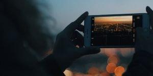 Handybild von den Lichtern einer Stadt bei Sonnenuntergang