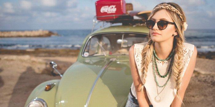 Grüner VW Käfer mit roter Coca Cola Kiste und einen jungen Frau mit Sonnenbrille