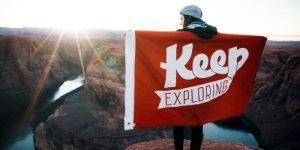 Eine Work and Travellerin steht mit einer Flagge an einem Canyon