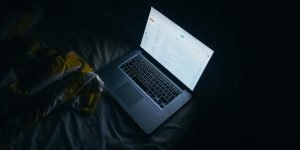 Gelbe Decke, weißes Bettlaken und ein Computer mit leuchtendem Bildschirm