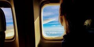 Ein Frau sitzt im Flugzeug und guckt durchs Fenster
