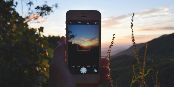 Ein Handy in der Had halten und Fotos von der Natur und der Landschaft machen