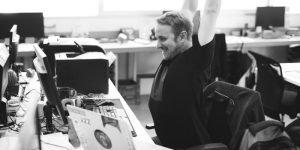 Ein Mann streckt sich und drum herum stehen Drucker und Pcs