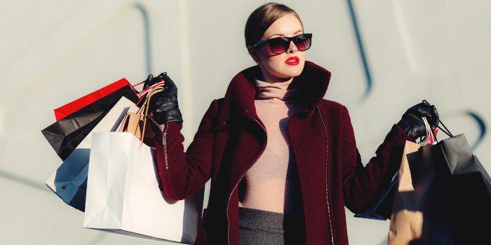 Eine Frau mit Sonnenbrille und rotem Mantel kommt trägt mehrere Einkaufstüten mit sich rum
