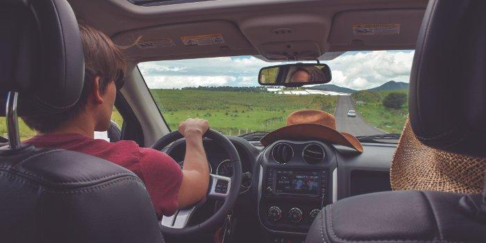 Ein Junge mit Sonnebrille fährt einen Mietwagen