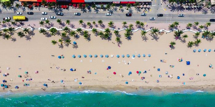 Luftaufnahme vom Strand und vielen Urlaubern mit Sonnenschirmen