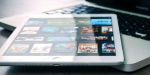 Win Aplle Tablet und ein Apple Macbook liegen auf einem holffarbenen Tisch