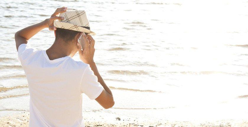 Junger Mann telefoniert am Strand