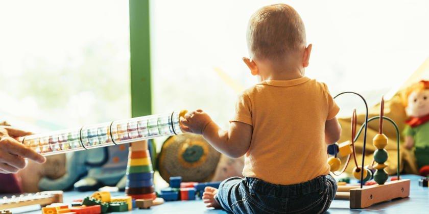 Kind umgeben von viel Spielzeug.