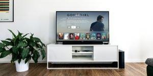 Wohmzimmer mit dunklem Holzpakett, einerm großen UHD Fernseher auf dem die Filmauswahl eines Streaming Anbieters zu sehen ist